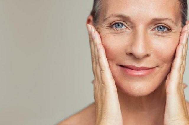 Retrato de uma bela mulher idosa a tocar na sua pele perfeita e a olhar para a câmara. Rosto de mulher madura com rugas massageando o rosto isolado sobre fundo cinza. Conceito de processo de envelhecimento.Fonte: 220212186<!-- NICAID(14316773) -->