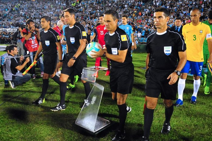 Luiz Zini Pires. Referee Patricio Loustau (C) and linesmen enter the field  at the start of the f6ebbfe761307