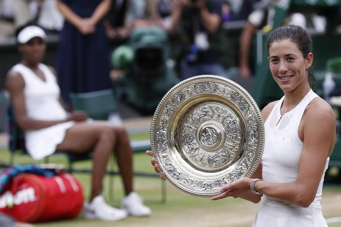 Spains Garbine Muguruza holds up The Venus Rosewater Dish as she celebrates beating US player Venus Williams to win the womens singles final on the twelfth day of the 2017 Wimbledon Championships at The All England Lawn Tennis Club in Wimbledon, southwest London, on July 15, 2017. Muguruza won 7-5, 6-0. / AFP PHOTO / Adrian DENNIS / RESTRICTED TO EDITORIAL USE