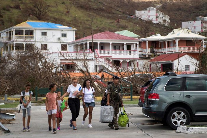 A soldier escorts a family leaving Saint-Martin at Grand-Case Esperance airport, on September 10, 2017 on the French Carribean island of Saint-Martin after it was devastated by Irma hurricane. People on the islands of Saint Martin and Saint Barts turn to the colossal task of rebuilding after Hurricane Irma laid waste to their infrastructure and shattered their lives. / AFP PHOTO / Martin BUREAU