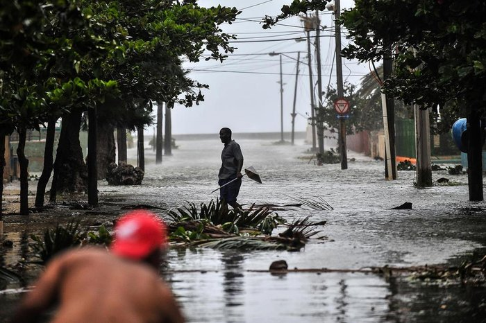 A man walks in a flooded street during the passage of Hurricane Irma in Havana, on September 9, 2017.  Irmas blast through the Cuban coastline weakened it to a Category Three, but it is still packing winds of 125 miles (200 kilometer) per hour. / AFP PHOTO / YAMIL LAGE
