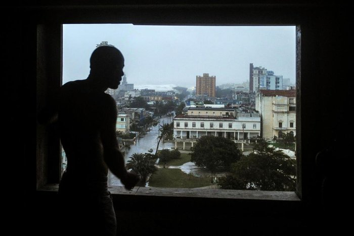 A man looks from the window at flooded streets, during the passage of Hurricane Irma in Havana, on September 9, 2017.  Irmas blast through the Cuban coastline weakened it to a Category Three, but it is still packing winds of 125 miles (200 kilometer) per hour. / AFP PHOTO / YAMIL LAGE