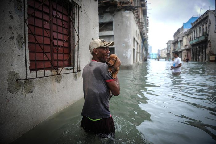 Cubans wade through a flooded street in Havana, on September 10, 2017. Deadly Hurricane Irma battered central Cuba on Saturday, knocking down power lines, uprooting trees and ripping the roofs off homes as it headed towards Florida. Authorities said they had evacuated more than a million people as a precaution, including about 4,000 in the capital.  / AFP PHOTO / YAMIL LAGE