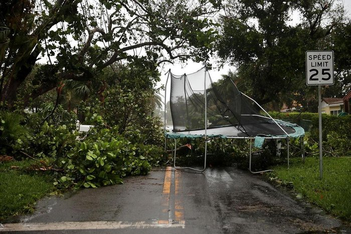 POMPANO BEACH, FL - SEPTEMBER 10: Downed trees and a windblown trampoline block a street as Hurricane Irma hits the southern part of the state September 10, 2017 in Pompano Beach, Florida. The Category 4 hurricane made landfall in the United States in the Florida Keys at 9:10 a.m. after raking across the north coast of Cuba.   Chip Somodevilla/Getty Images/AFP