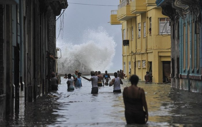 Cubans wade through a flooded street in Havana, on September 10, 2017. Deadly Hurricane Irma battered central Cuba on Saturday, knocking down power lines, uprooting trees and ripping the roofs off homes as it headed towards Florida. Authorities said they had evacuated more than a million people as a precaution, including about 4,000 in the capital.  YAMIL LAGE / AFP