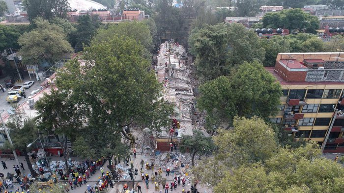 Aerial view showing as rescuers, firefighters, policemen, soldiers and volunteers search for survivors in a flattened building in Mexico City on September 20, 2017 a day after a strong quake hit central Mexico. A powerful 7.1 earthquake shook Mexico City on Tuesday, causing panic among the megalopolis 20 million inhabitants on the 32nd anniversary of a devastating 1985 quake. / AFP PHOTO / Mario VAZQUEZ