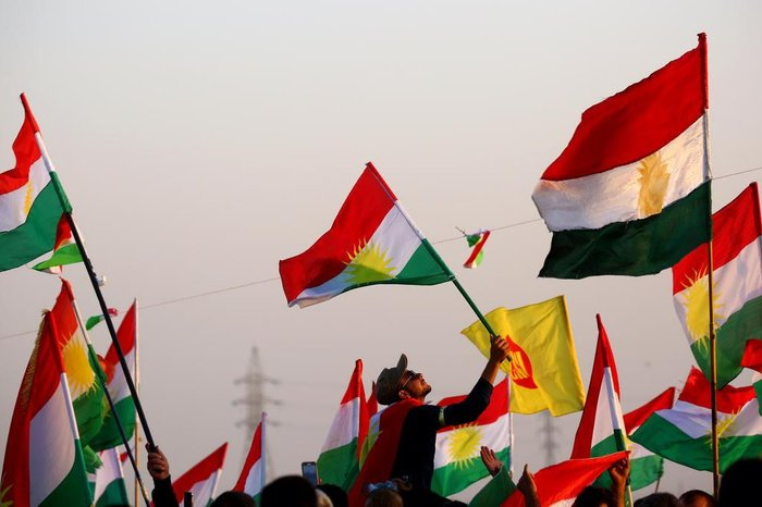 Syrian Kurds wave the Kurdish flag, in the northeastern Syrian city of Qamishli on September 27, 2017, during a gathering in support of the independence referendum in Iraqs autonomous northern Kurdish region. Iraqs Kurds announced a massive yes vote for independence following a referendum that has incensed Baghdad and sparked international concern. / AFP PHOTO / DELIL SOULEIMAN