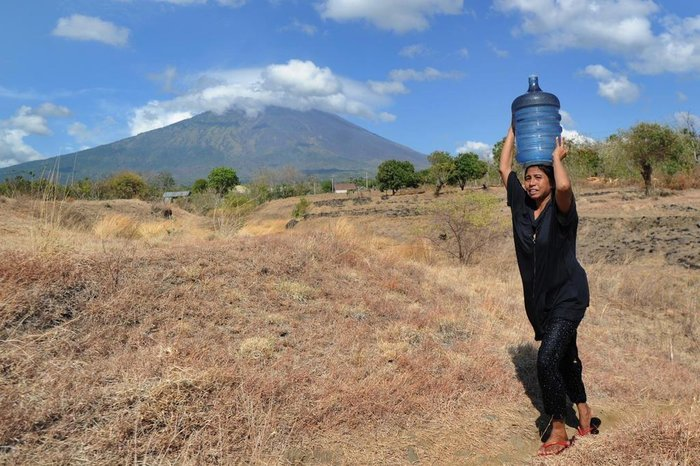A woman carries water on her head in the Kubu subdistrict of Karangasem Regency on the Indonesian resort island of Bali on September 26, 2017, as Mount Agung volcano looms in the background. More than 57,000 people have fled a volcano on the tourist island of Bali as rising magma and increased tremors fuel fears of an imminent eruption, officials said on September 26. / AFP PHOTO / SONNY TUMBELAKA