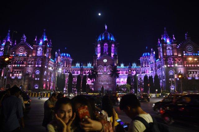 Indianos na frente da estação de trem Chhatrapati Shivaji Terminus (CST) antes das celebrações da véspera de Ano Novo em Mumbai em 31 de dezembro de 2017.