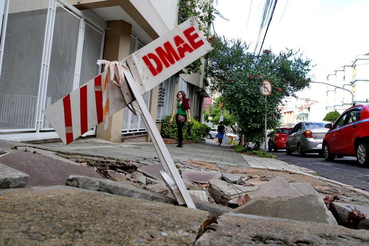 Moradores aguardam desde o ano passado por conserto de cratera na calçada da Rua Miguel Tostes