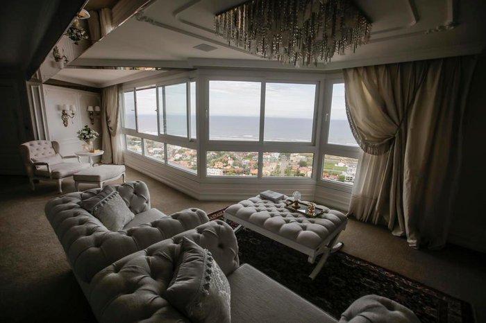 Cortinas e lustres clássicos decoram a sala de estar